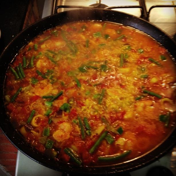 Paella com caldo cozinhando